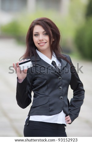 Attractive business woman on background of building. Cute business woman showing plastic card looking at camera