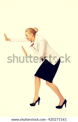 Attractive business woman pushing something - stock photo