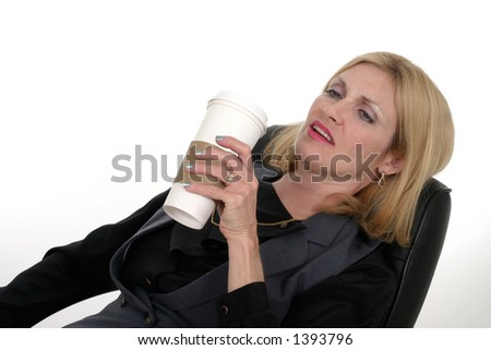 Attractive business woman relaxing at her desk with a cup of coffee in a popular but generic paper coffee cup.