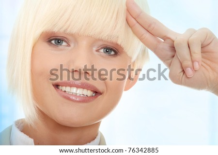 Attractive business woman saluting. Over abstract blue background - stock photo