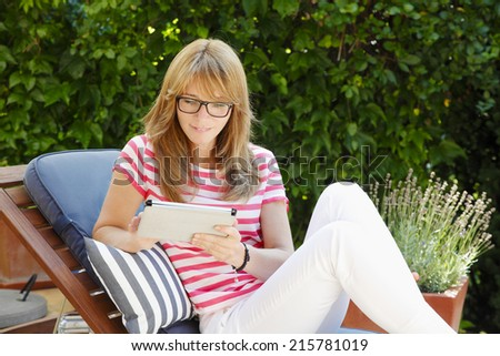 Attractive business woman sitting at garden, while working at home with digital tablet. Small business.  - stock photo