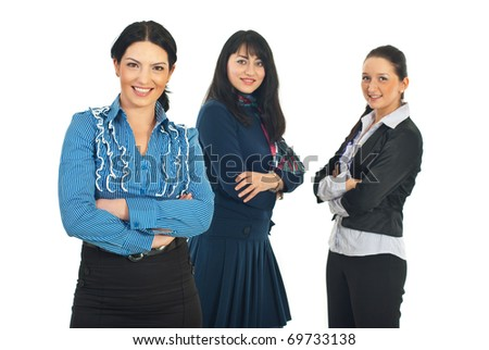 Attractive business woman  standing with arms folded in front of camera and her team of women smiling in background - stock photo