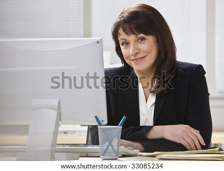 Attractive business woman stting at desk behind computer monitor smiling at camera. Horizontal. - stock photo