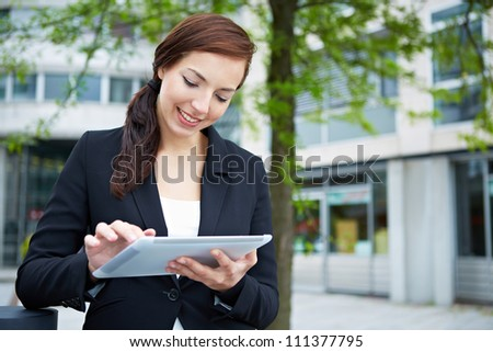 Attractive business woman using tablet computer on the way in the city - stock photo