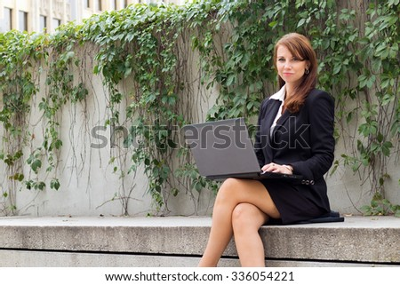 Attractive business woman with laptop outdoors - copyspace - stock photo