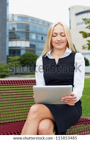 Attractive business woman with tablet computer on a park bench - stock photo