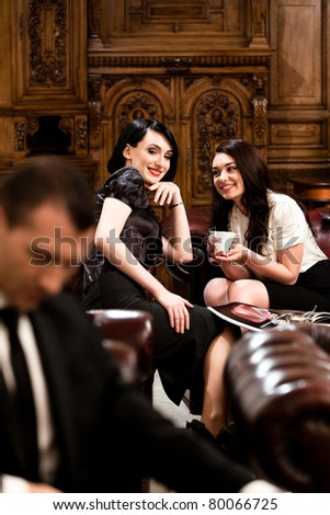 Attractive business women chatting while is looking at a handsome man in foreground. Please see more images from the same shoot. - stock photo