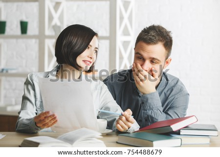 Attractive businessman and woman doing paperwork at office desk with pile of books. Exam concept