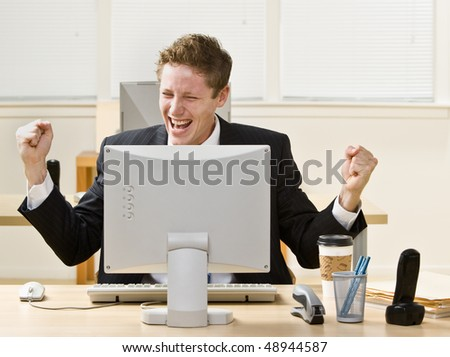 Attractive Businessman cheering at desk. Horizontally framed shot.
