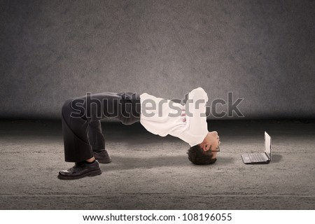 Attractive businessman doing breakdance style with laptop computer - stock photo
