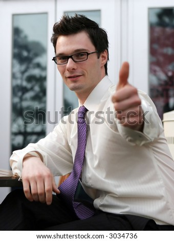 Attractive businessman gives the thumbs up signal (focus on model's face). - stock photo