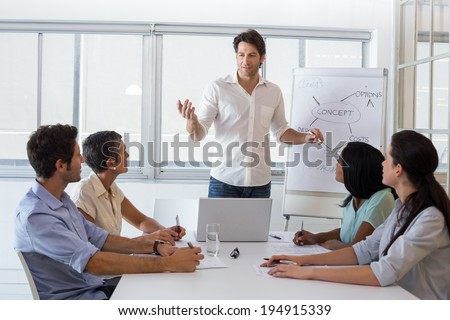 Attractive businessman giving a presentation to his employees in the office - stock photo