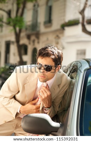 Attractive businessman grooming himself using a car mirror outdoors, tightening his tie knot. - stock photo