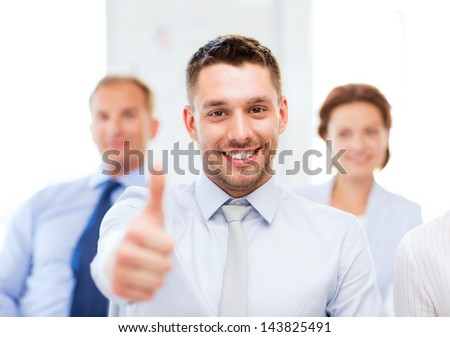 attractive businessman in office showign thumbs up - stock photo