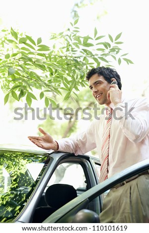 Attractive businessman leaning on a car's top while making a phone call in a leafy street, smiling. - stock photo