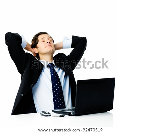 Attractive businessman leans his head back into his hands and closes his eyes, daydreaming about his holiday - stock photo