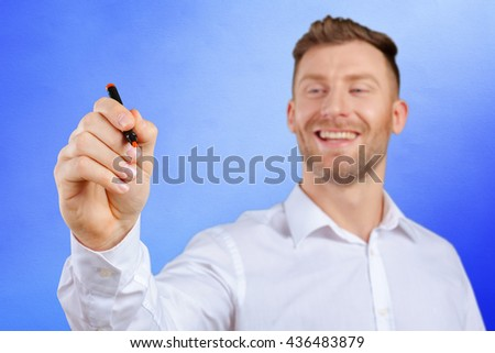attractive businessman or teacher with marker writing or drawing something - stock photo