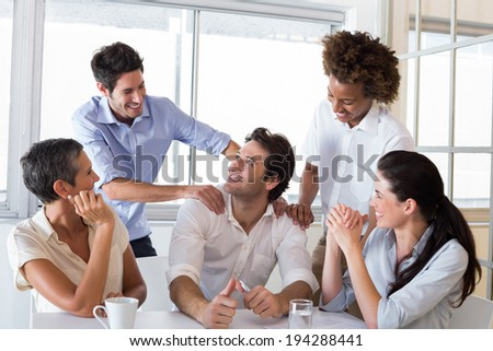 Attractive businessman praising coworker during a meeting - stock photo