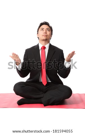 Attractive businessman praying for a great year. Wearing a suit and tie, sitting on a yoga mat. White background.