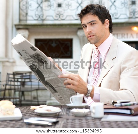 Attractive businessman reading the newspaper while having breakfast in an elegant luxury coffee shop, outdoors. - stock photo