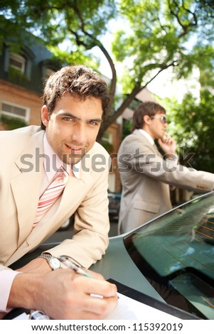 Attractive businessman smiling at the camera while working outdoors with a colleague, leaning on a luxury car in a tree aligned street. - stock photo