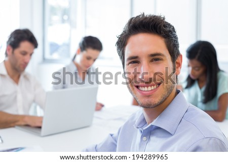 Attractive businessman smiling at the camera whilst working with coworkers - stock photo