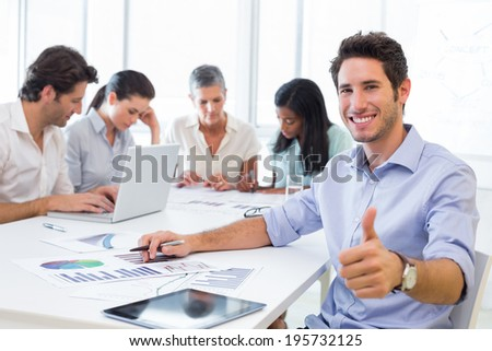 Attractive businessman smiling at the camera whilst working with coworkers in the background - stock photo