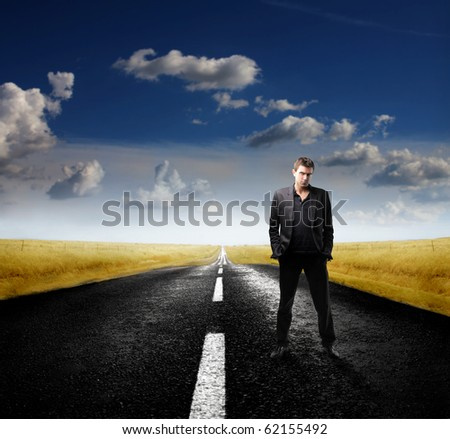 Attractive businessman standing on a road