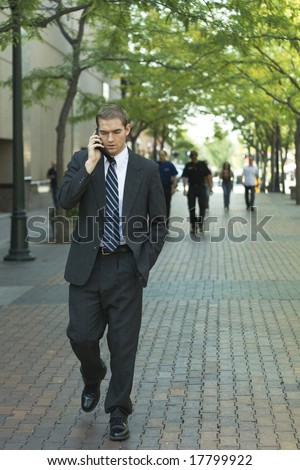 Attractive businessman talking on a cell phone outside, downtown - stock photo