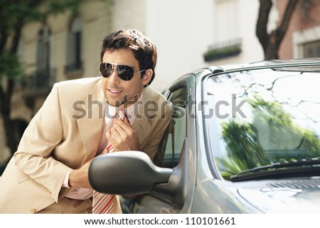 Attractive businessman tightening his tie while looking at himself in a car's reversing mirror, smiling. - stock photo