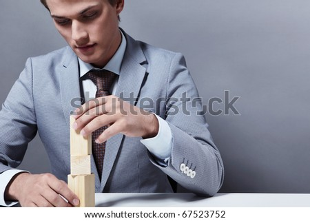 Attractive businessman to build a tower on a gray background - stock photo