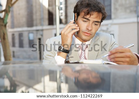 Attractive businessman using a cell phone and taking notes while leaning on a car in the city. - stock photo