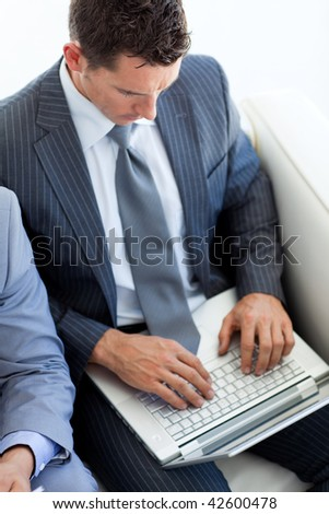 Attractive businessman using a laptop while waiting for a job interview in an office