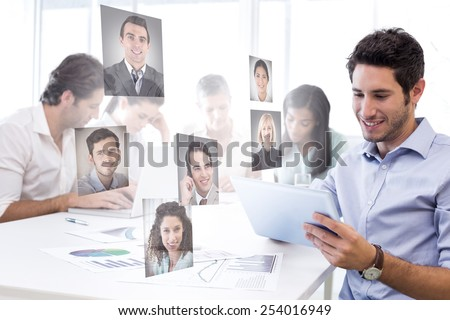 Attractive businessman using a tablet at work against profile pictures