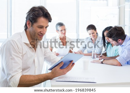 Attractive businessman using tablet device at work while coworkers work in the background