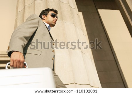 Attractive businessman walking up the stairs of a large building, holding a metallic briefcase and wearing shades. - stock photo