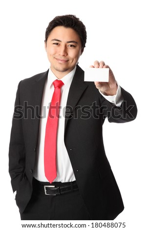 Attractive businessman wearing a suit and tie holding up a blank business card. White background. - stock photo