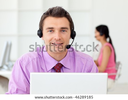 Attractive businessman with headset on in the office - stock photo