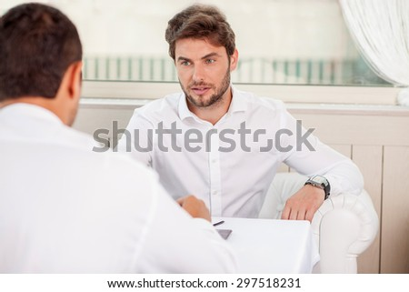 Attractive businessmen are sitting in restaurant and looking at each other seriously. They are talking about their work and sharing main ideas - stock photo