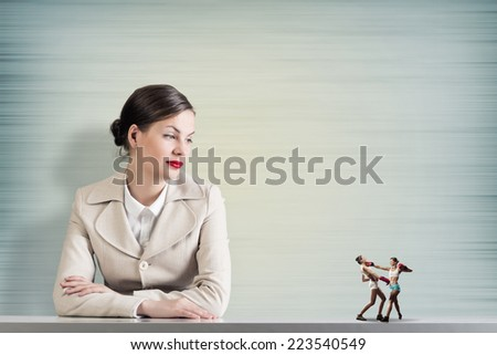 Attractive businesswoman and miniatures of two boxing women - stock photo