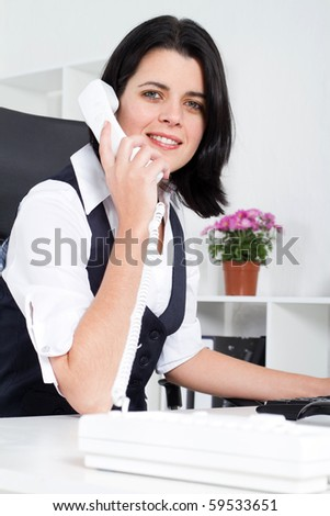 attractive businesswoman answering telephone in office - stock photo