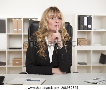 Attractive businesswoman asking for silence or for a project or agreement to be kept a secret, as she sits at her desk with her finger raised to her lips. - stock photo