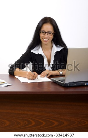 attractive businesswoman at her desk signing papers
