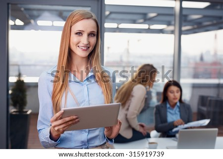 Attractive businesswoman at office standing with digital tablet - stock photo