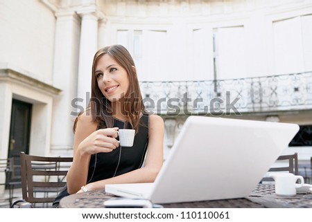 Attractive businesswoman drinking coffee and using a laptop computer while sitting at a coffee shop's terrace table.