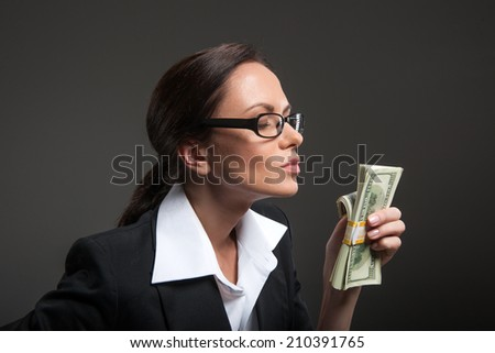 Attractive businesswoman enjoys smell of money on black background. Young woman holding hundred dollar bill stack - stock photo