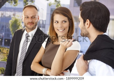 Attractive businesswoman flirting with colleague in front of office center, outdoors. Suit and tie, ring. - stock photo