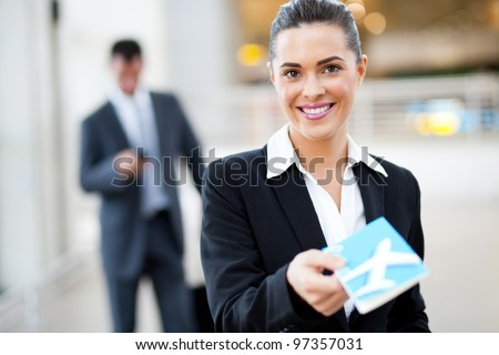 attractive businesswoman handing over air ticket at airport check in counter
