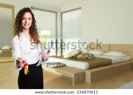 attractive businesswoman handing over keys to an apartment - stock photo