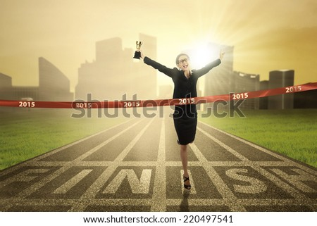 Attractive businesswoman holding a trophy in the finish line with number 2015 - stock photo